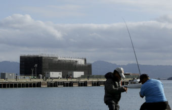 "Two men fish in the water in front of a barge on Treasure Island in San Francisco on Tuesday. An unnamed source tells CBS the barge carries a building ""constructed of interchangeable 40-foot shipping containers that can be assembled and disassembled at will, allowing it to be placed on barges, trucks or rail cars and taken anywhere in the world."" Jeff Chiu/AP"