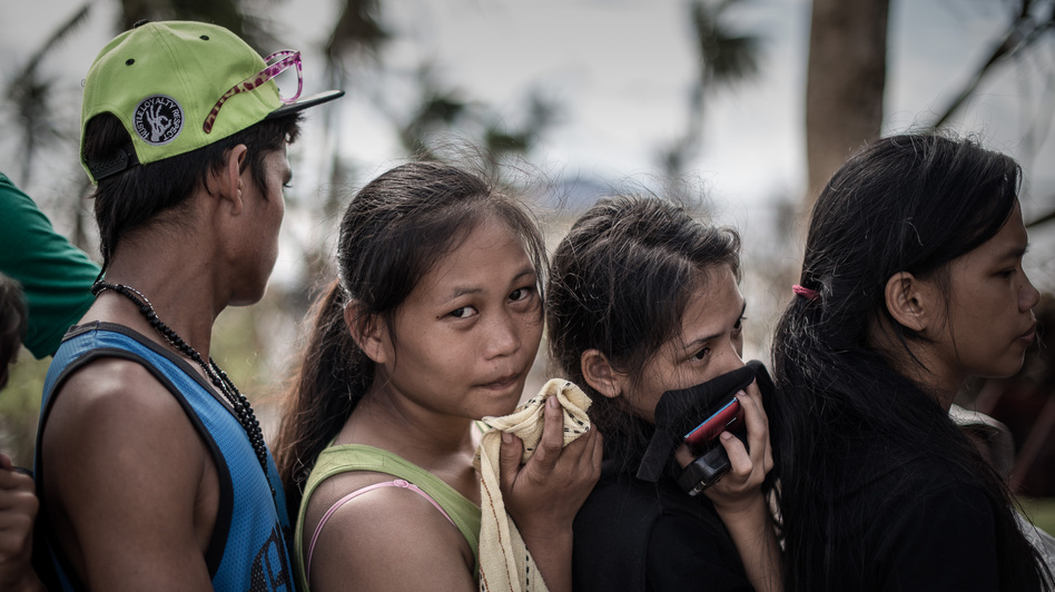 In Tacloban, the Philippines, on Thursday, some survivors waiting in a line to charge cellphones covered their faces because of the lingering smell of dead bodies. Philippe Lopez /AFP/Getty Images