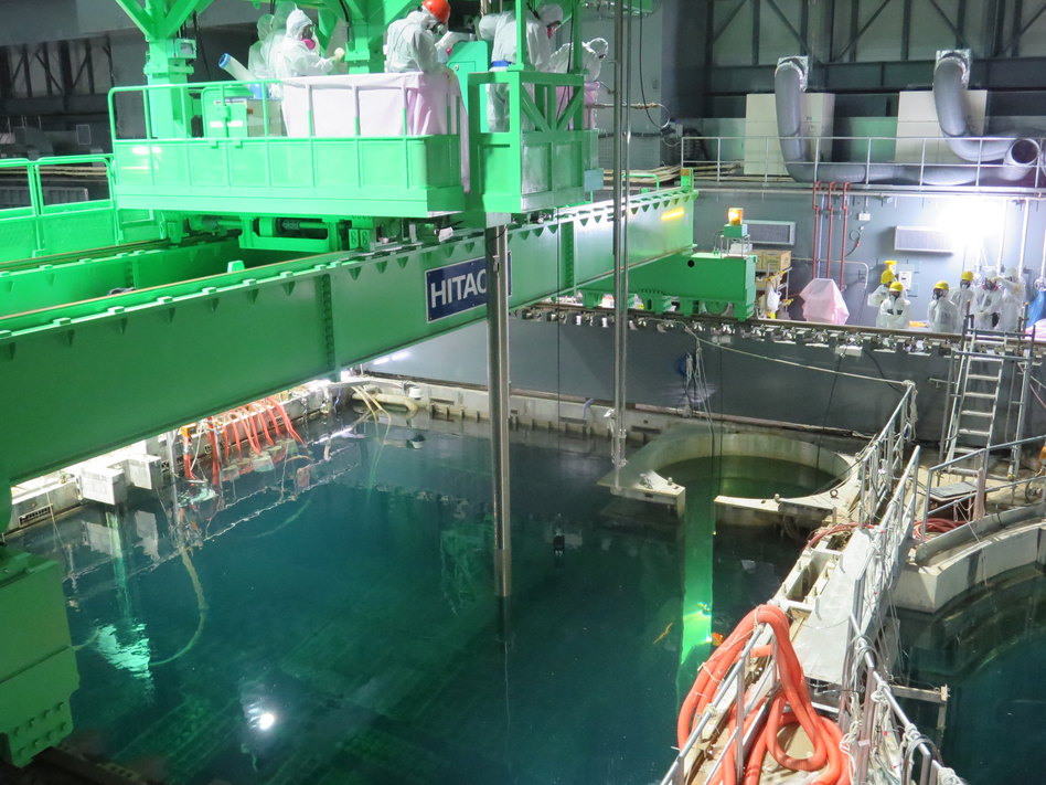 Workers remove nuclear fuel rods from a pool at the Unit 4 reactor of the Fukushima Daii-chi nuclear power plant on Monday. Handout/TEPCO
