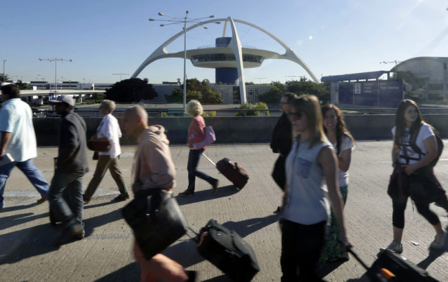 People exit Los Angeles International Airport in Los Angeles on Friday. Gregory Bull/AP