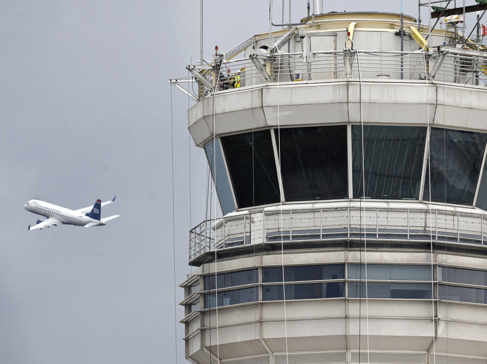 A passenger jet flies past the FAA control tower at Washington's Ronald Reagan National Airport. Cliff Owen/AP