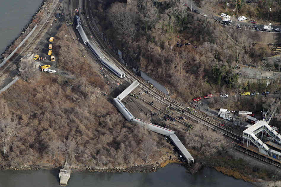 A Metro-North passenger train derailed in the Bronx borough of New York on Sunday, coming to a rest just feet from the water. Authorities say four people were killed and 63 injured. Mark Lennihan/AP