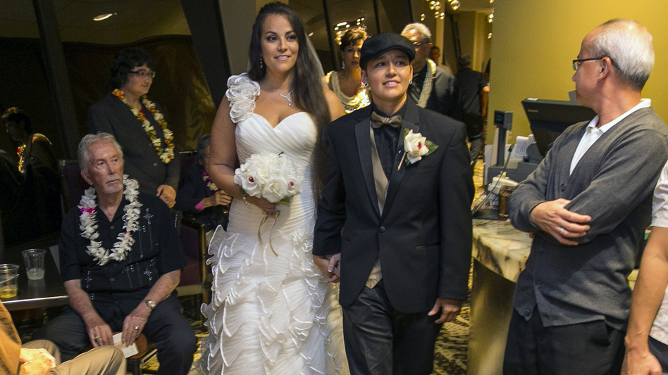 Saralyn Morales, center left, and Isajah Morales walk down the aisle at the Sheraton Waikiki in Honolulu Monday, shortly after Hawaii's new gay marriage law took effect. Marco Garcia/AP
