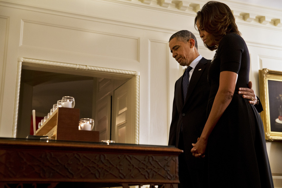 President Obama and first lady Michelle Obama take a moment of silence in honor of the Newtown shooting victims on the one year anniversary of the tragedy. Jacquelyn Martin/AP