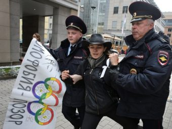 "Sept. 25: Police detain a gay rights activist in Moscow. The poster, adorned with Olympic rings, reads ""Homophobia is the shame of Russia!"" Alexander Nemenov/AFP/Getty Images"