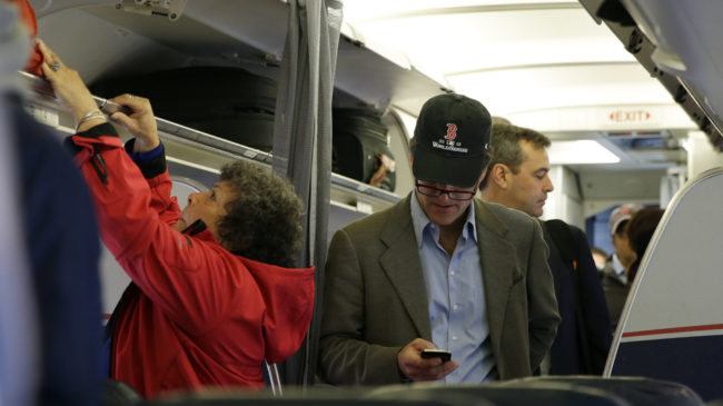 A passenger checks his cellphone while boarding a flight in Boston. The Federal Communications Commission is proposing new rules to allow using cellphones for data and voice calls during airline flights. Matt Slocum/AP