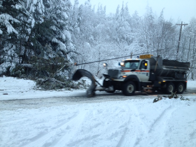 A state Department of Transportation plow truck clears debris near a downed power line on New Year's Eve morning. Photo courtesy Sallie Regan.