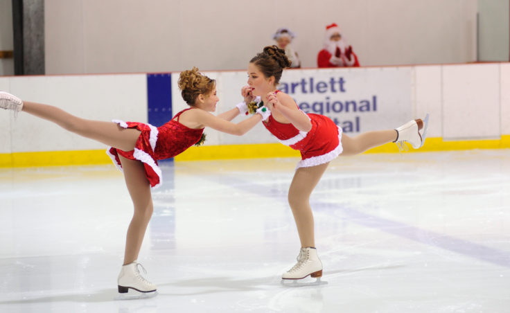 Grace Walli and Katie McKenna close out their routine with Santa and Mrs. Claus applauding in the backdrop during Juneau Skating Club's annual holiday recital.