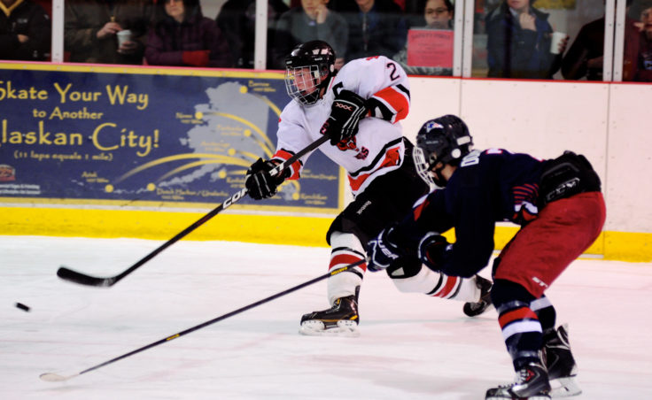 Juneau captain Grant Ainsworth gets a shot off while being covered by North Pole defender Jason Donald during the team's two-game, weekend series at Treadwell Ice Arena.