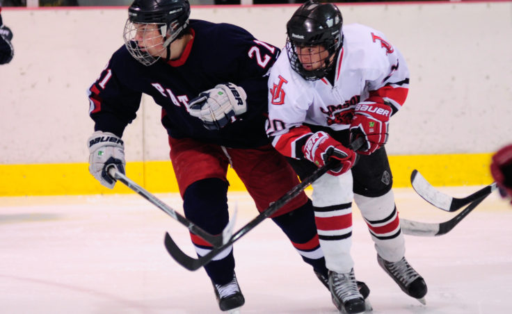 Juneau's Corey Box (right) lifts North Pole's James Laszoffy's stick, preventing him from getting a pass during Friday night's game at Treadwell Ice Arena.