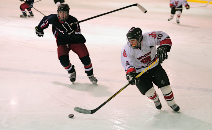 Juneau's Ethan Sied tries to stay a few strides ahead of North Pole's AJ Hebert during the two-game series at Treadwell Ice Arena.