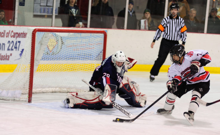 Juneau forward Kaipo Tseu returns to the ice for Juneau with one of several weekend attempts on North Pole goalie Allan Heineken.