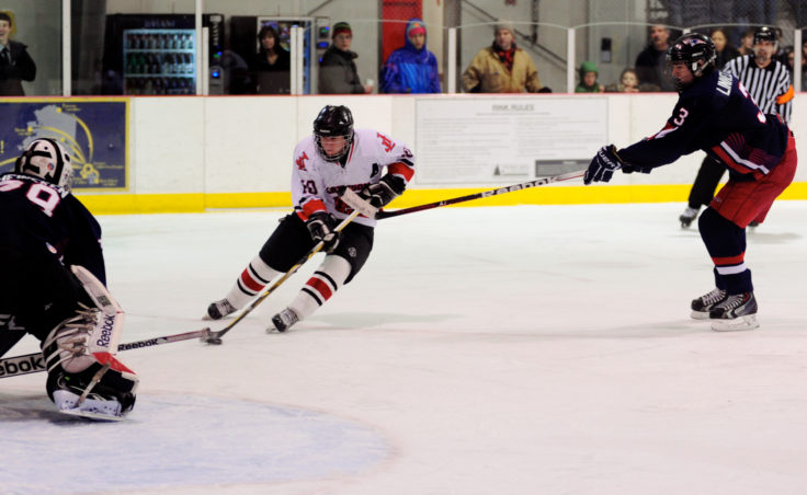 Juneau center Ethan Seid skates past North Pole defenseman Carson Linnell in a scoring attempt on North Pole goalie Allan Heineken.