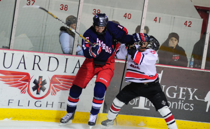 North Pole's Thomas Rojas gives Juneau's Kaipo Tseu a playful shove along the boards during the two-game series at Treadwell Ice Arena.