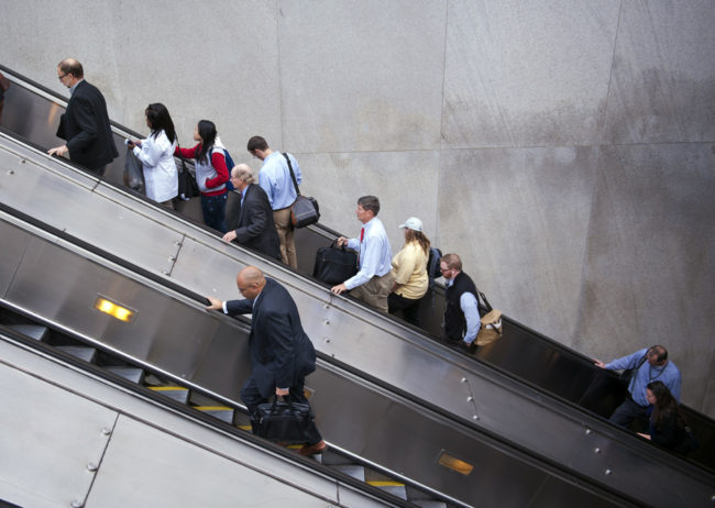 People exit a Metro subway station, by escalator, along Pennsylvania Ave., NW, in Washington. Cliff Owen/AP