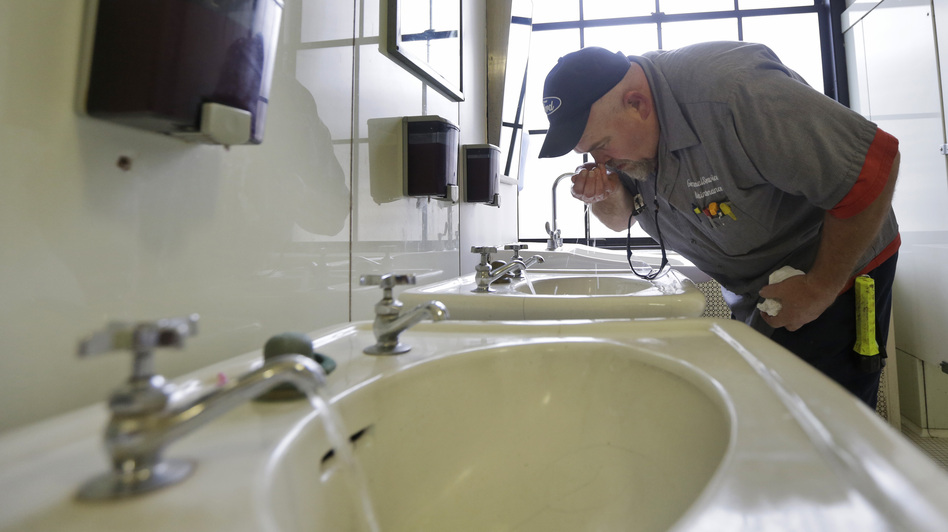 In West Virginia, a ban on water use has been lifted in at least three areas affected by a chemical spill. Here, Al Jones of the state's General Services department tests the water as he flushes a faucet and opens a restroom on the first floor of the Capitol in Charleston on Monday. Steve Helber/AP