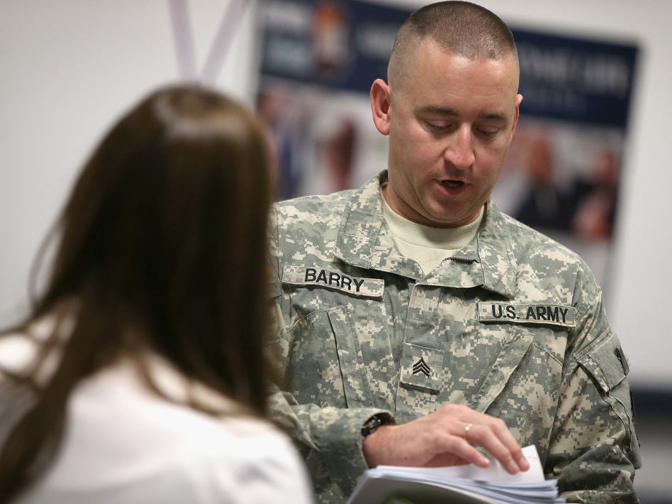 Sgt. Troy Barry (right), with the Army National guard, speaks with Katie Sogar with Rivers Casino during a job fair for veterans in September. Scott Olson/Getty Images