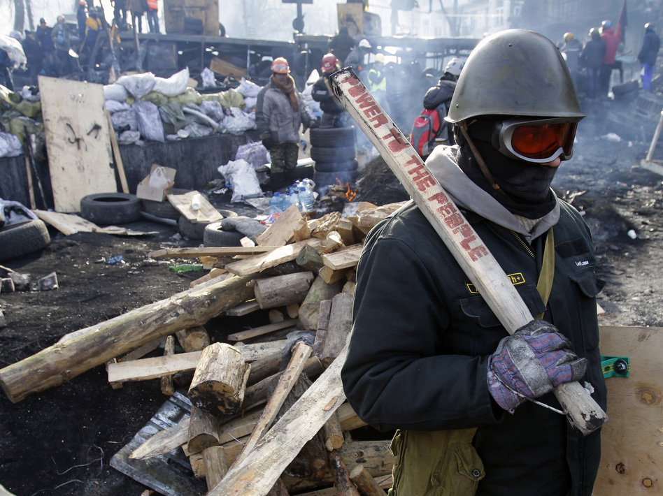 A protester guards a barricade in Kiev, Ukraine, on Monday. Darko Vojinovic/AP