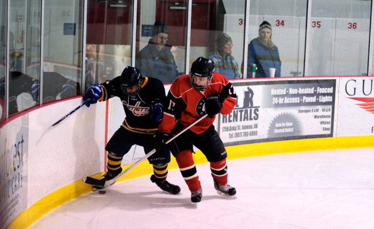 Juneau's Zach Easton battles with Bartlett's Raphael Turner during the weekend series at Treadwell Ice Arena.