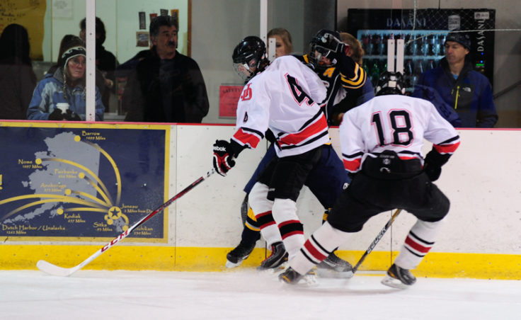 Juneau's Oscar Jones checks Bartlett's Kyle Sun along the boards while teammate Logan Coleman goes after the puck.