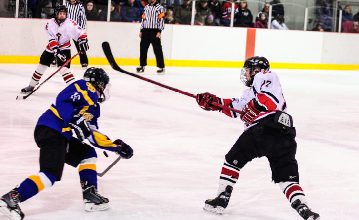 Juneau defenseman Michael Dale unleashes a shot from the point but Monroe Catholic's Rodney Gliffey gets a stick on it.