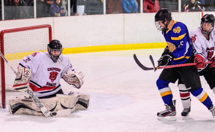 Juneau goalie Neal Chapman gets the call for Saturday night's game and turns aside this shot with teammate Michael Dale holding off Monroe Catholic's Grand Olson.