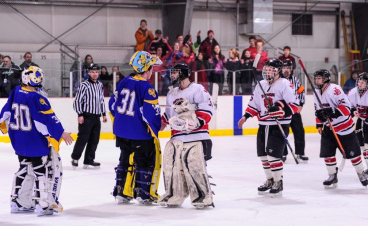 Juneau goalie Neal Chapman leads the traditional postgame handshake greeting counterpart Monroe Catholic's Nathaniel Brose, who turned back 65 shots in two games against Juneau.