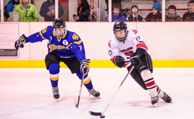 Juneau's Zach Easton maintains possession while trying to elude Monroe Catholic's Hunter Haman during the weekend series at Treadwell Ice Arena.