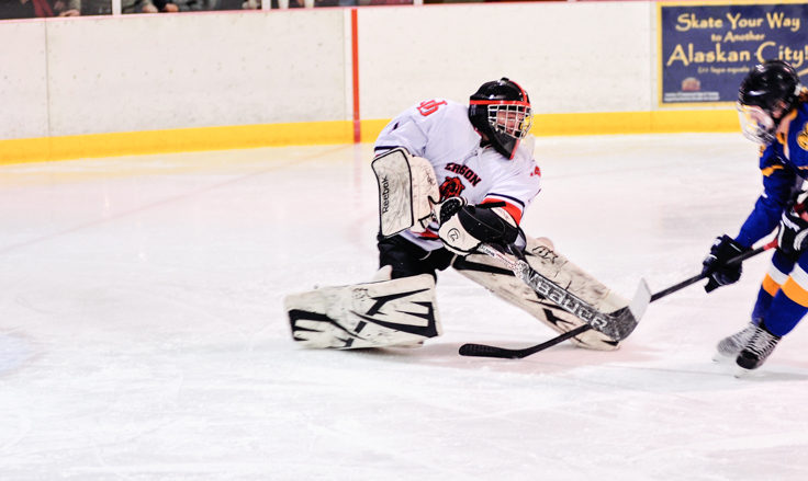 Juneau goalie Liam McDermott beats Monroe Catholic's Dylan Steele to the puck before Steele can get off a shot.