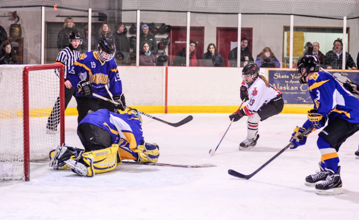 Juneau's Kate Metcalf finds herself in the middle of four Monroe Catholic players, including goalie Nathaniel Brose smothering Metcalf's shot.