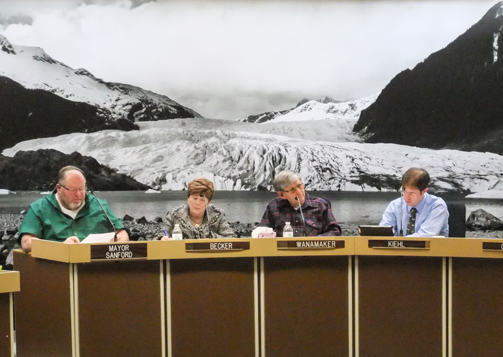 Noting the photo behind Assembly members, North Douglas resident Gene Randall compared a cellphone tower on Spuhn Island to a fictitious one at the Mendenhall Glacier. (Photo by Rosemarie Alexander/KTOO)