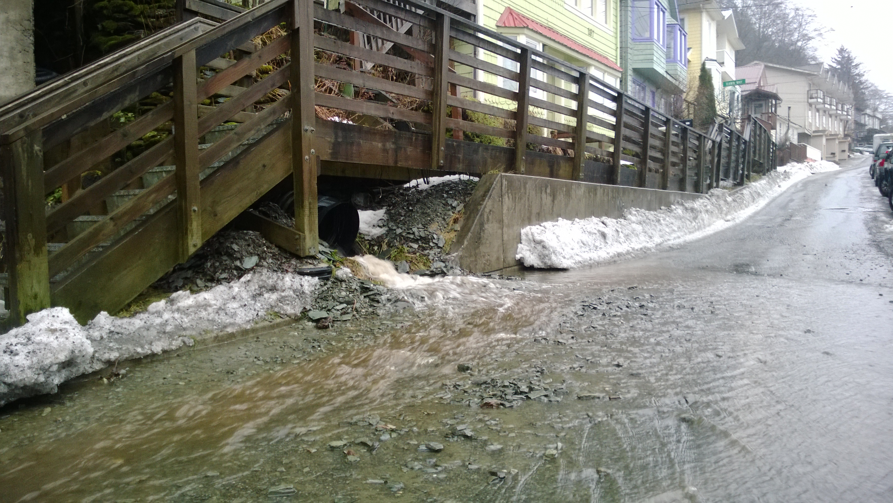 Muddy water and small debris gush from a culvert onto Gastineau Avenue on Tuesday. (Photo by Jeremy Hsieh/KTOO)