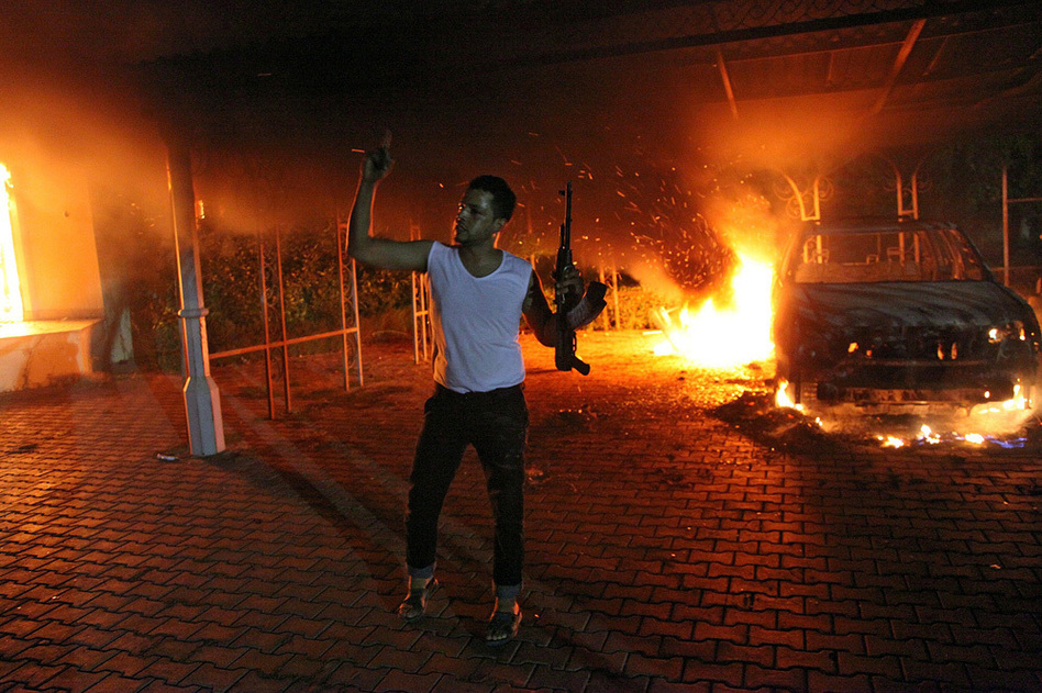An armed man waves his arms as buildings and cars are engulfed in flames after being set on fire inside the U.S. Consulate compound in Benghazi late on Sept. 11, 2012. AFP/Getty Images