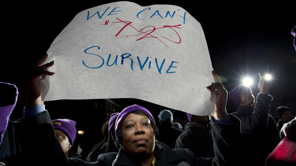 Darlene Handy of Baltimore holds up a banner at a rally supporting a pay measure in Maryland. More than 20 states have raised minimum pay rates above the federal level. Jose Luis Magana/AP