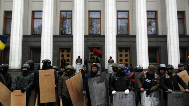 Anti-government protesters stand guard in front of Ukraine's parliament in Kiev on Saturday. (Marko Drobnjakovic/AP)