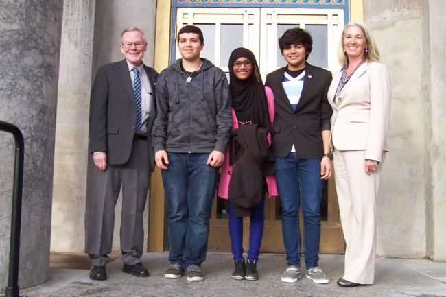Exchange students from the Middle East Haytham Mohanna, Maha Abdulrazzaq, and Abdulla Husain pose with Sen. Dennis Egan and Rep. Cathy Munoz during a visit to the Capitol in January. (Photo courtesy of Alida Bus)