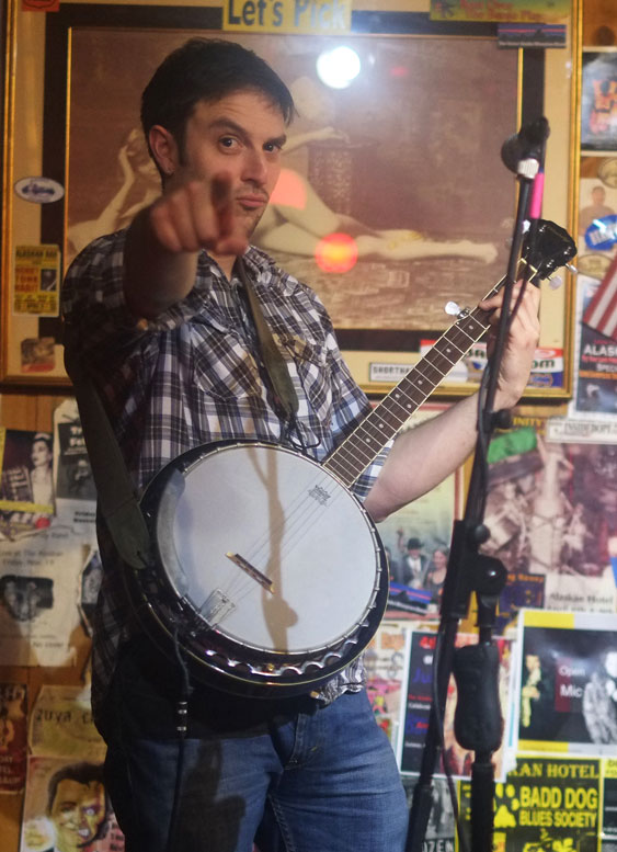 Man pointing onstage at Alaskan with banjo