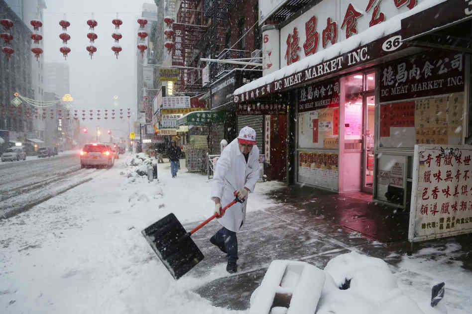 A man clears snow in front of DC Meat Market in the Chinatown neighborhood of New York City on Thursday. Snow and sleet are falling along the East Coast, from North Carolina to New England, a day after sleet, snow and ice bombarded the Southeast. Mark Lennihan/AP
