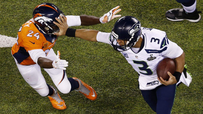 Quarterback Russell Wilson (#3) of the Seattle Seahawks stiff arms cornerback Champ Bailey (#24) of the Denver Broncos during Super Bowl XLVIII at MetLife Stadium on Sunday in East Rutherford, N.J. Jeff Zelevansky/Getty Images