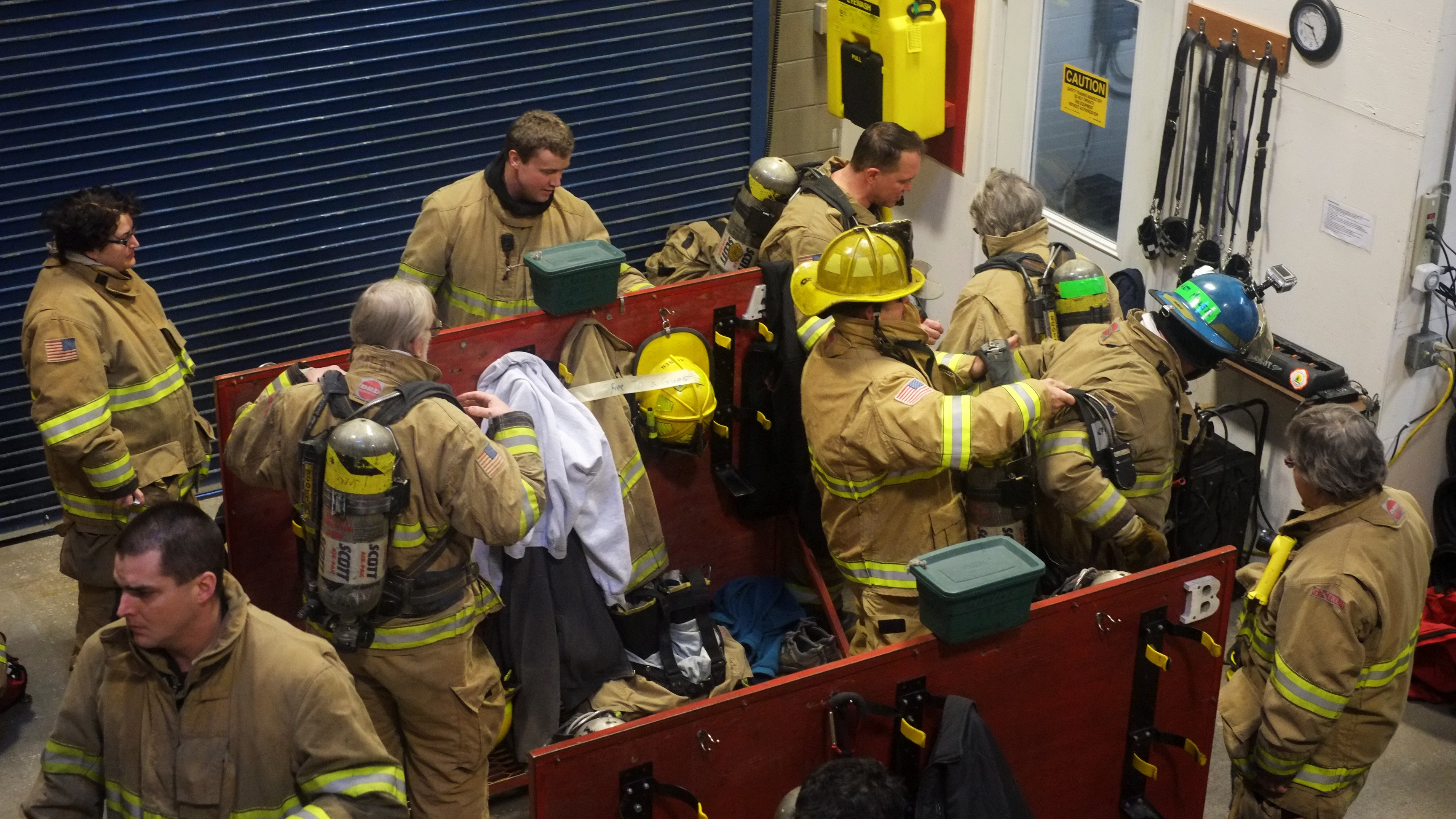 Participants and firefighters put on equipment for the first time at the safety training at Hagevig Fire Training Center. Photo by Annie Bartholomew/KTOO