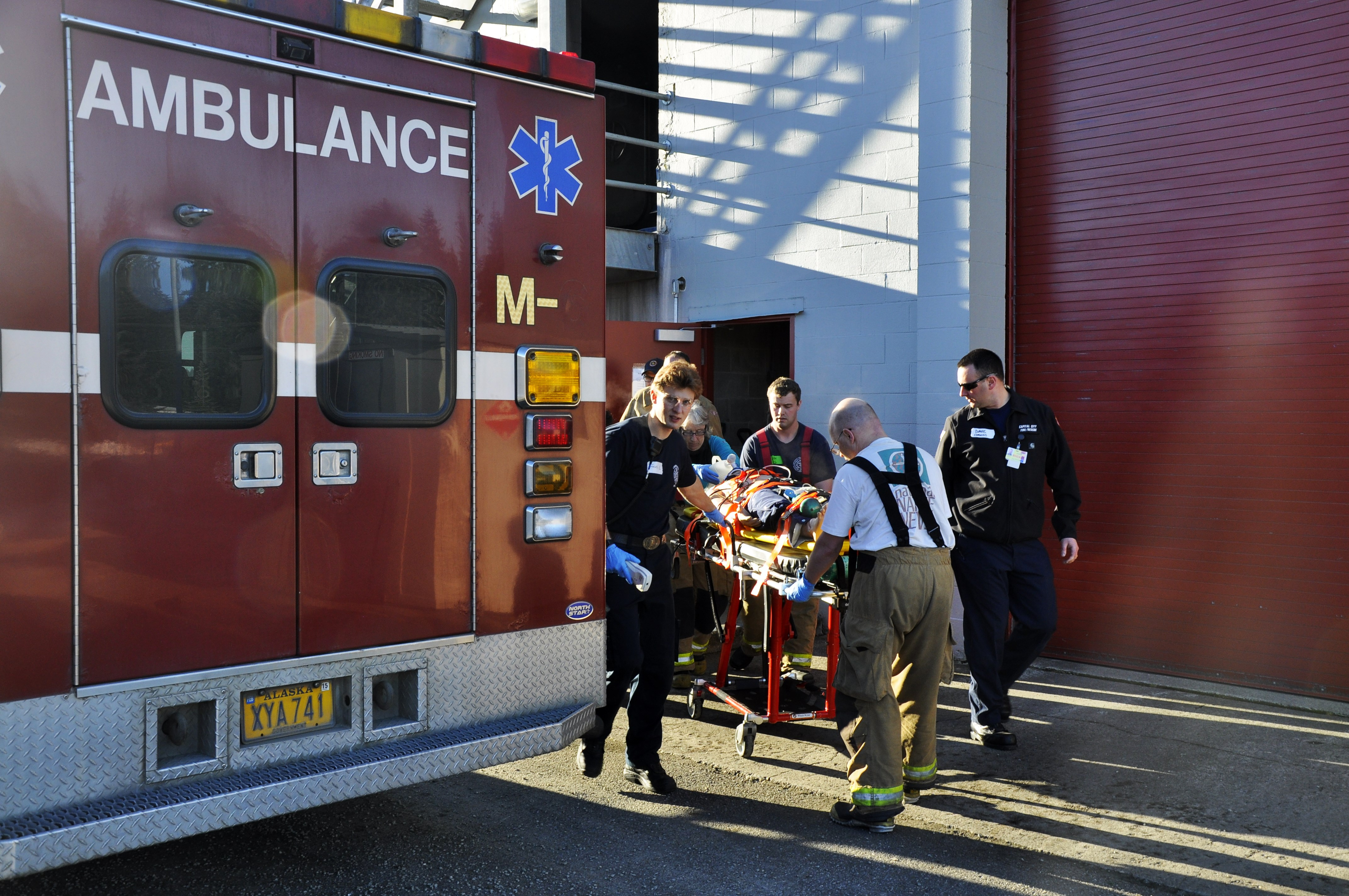 Participants rush the dummy into the ambulance as if it were a real patient at Hagevig Fire Training Center. (Photo by Annie Bartholomew/KTOO)