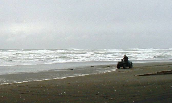 An ATVer rides along a Yakutat beach where a wave-energy system is to be installed. A Boston-based company will install the first device in 2015. (Ed Schoenfeld/CoastAlaska News)