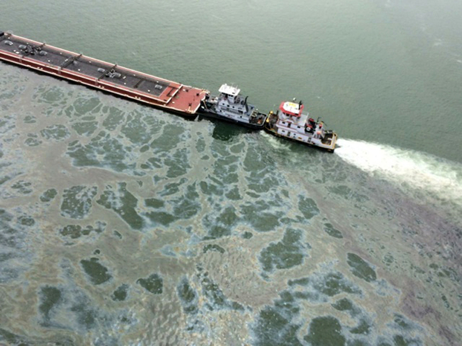 A barge loaded with marine fuel oil sits partially submerged in the Houston Ship Channel on Saturday. PO3 Manda Emery/ASSOCIATED PRESS