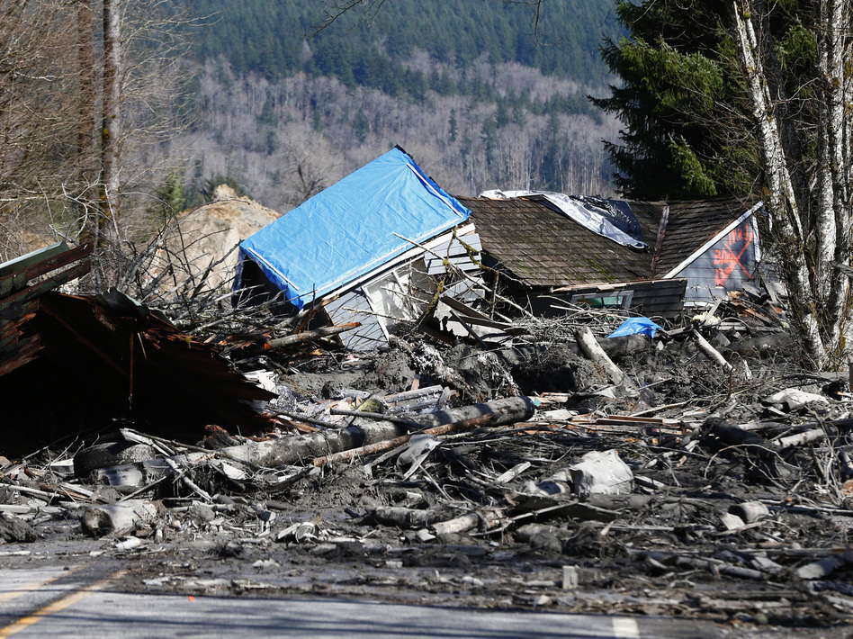 A destroyed house sits in muddy debris near Oso, Wash., on Sunday. A rain-soaked hillside let loose a wall of mud Saturday, inundating neighborhoods along the Stillaguamish River's North Fork. Lindsey Wasson/AP