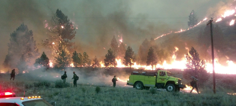 A U.S. Forest Service photo shows firefighters near the perimeter of the Elk Complex fire near Pine, Idaho, last summer. Lawmakers are calling for a change in the way America pays for wildfire disasters. AP