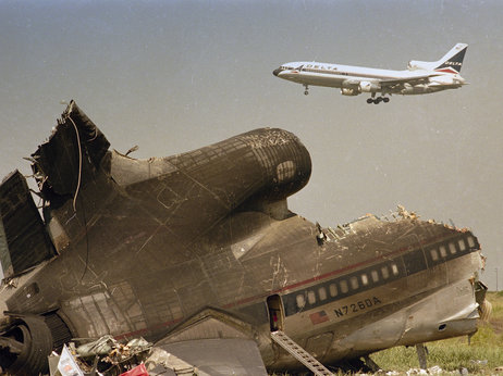 "The charred tail section of Delta Flight 191 sits near a runway at Dallas-Fort Worth International Airport in August 1985 after it crashed on approach. Delta quickly retired the ""191"" designation. Carlos Osorio/AP"