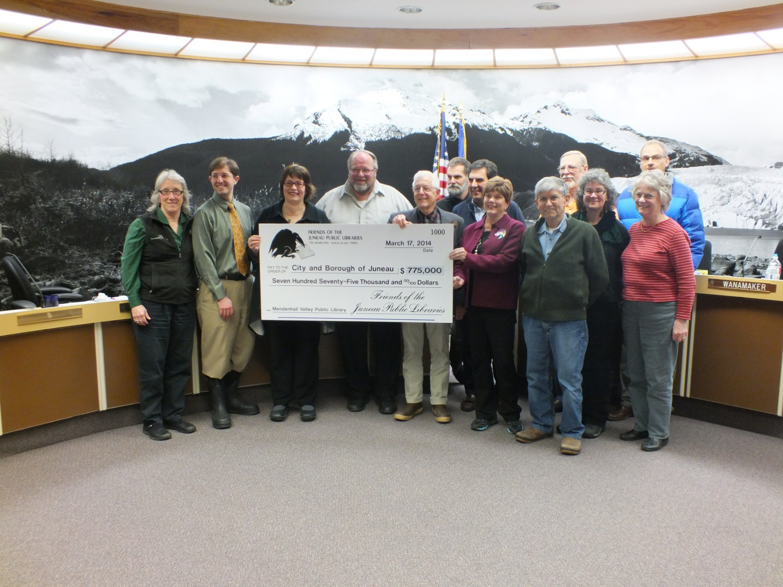 Members of the Juneau Assembly accept an oversize check for $775,000 from Friends of the Juneau Public Libraries. The money will go toward the new Mendenhall Valley library. (Photo by Casey Kelly/KTOO)