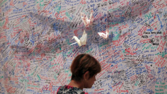 A woman reads messages for passengers aboard a missing Malaysia Airlines plane at a shopping mall in Kuala Lumpur, Malaysia on Saturday. Lai Seng Sin/AP