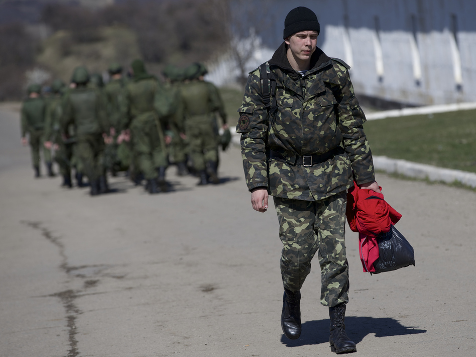 As Russian soldiers walked one way in the distance, a departing Ukrainian soldier carried some of his belongings Friday at a military base in Perevalne, Crimea. Ivan Sekretarev/AP
