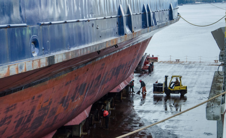 Shipyard workers clean the deck in preparation for lowering the Matanuska back into the water.